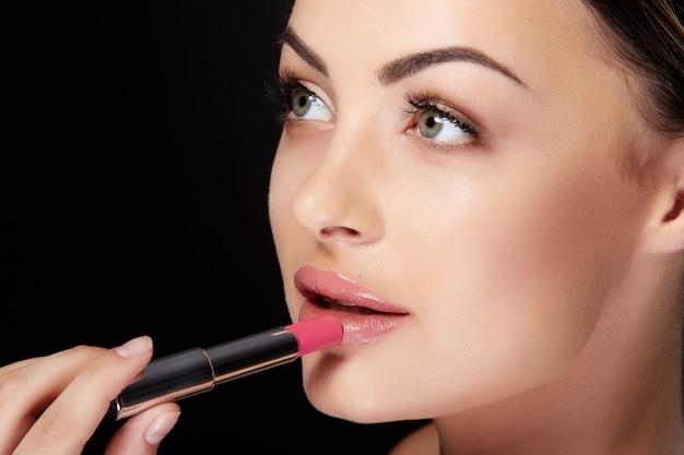 Conceito de beleza, perfil de jovem olhando de lado e pintando os lábios com batom rosa. closeup retrato de modelo com lábios rosados, estúdio com fundo preto