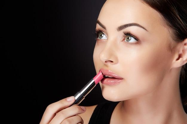 Conceito de beleza, perfil de jovem olhando de lado e pintando os lábios com batom rosa. retrato da beleza da modelo com lábios rosados, estúdio com fundo preto