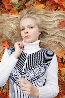 Conceito de beleza, pessoas, estação e saúde - menina bonita deitada em folhas de outono vermelhas e amarelas Foto Premium