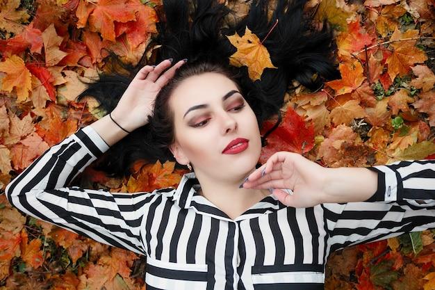 Conceito de beleza, pessoas, estação e saúde - menina bonita deitada em folhas de outono vermelhas e amarelas
