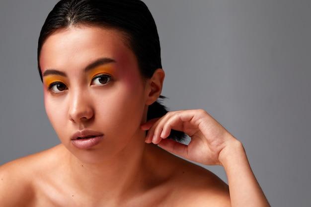 Conceito de beleza, uma linda mulher asiática com pele bonita e saudável em um fundo esmeralda.