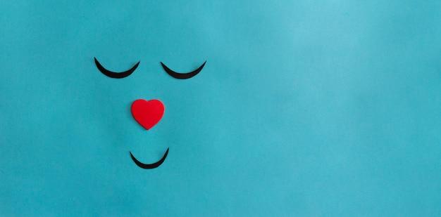 Conceito de bem-estar. rosto sorridente em fundo azul com nariz em forma de coração. copie o espaço.