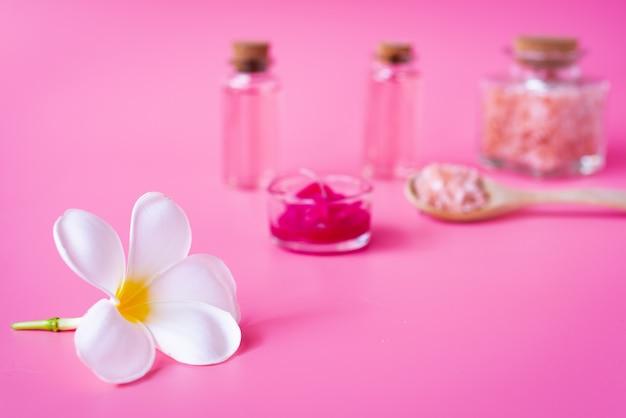 Conceito de bem-estar spa, flor branca plumeria, vela vermelha, sal marinho e rosa garrafa de sabonete líquido