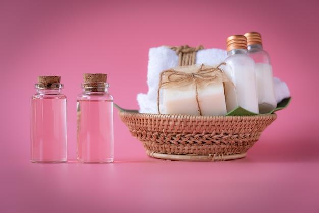 Conceito de bem-estar spa, garrafa de líquido rosa, sabão de leite, toalhas brancas