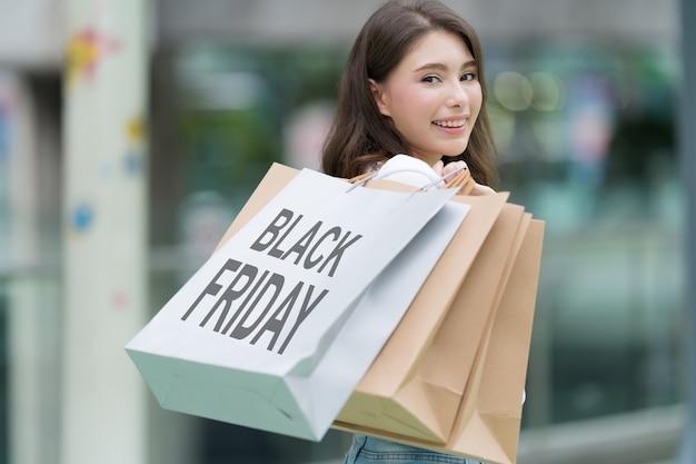 Conceito de black friday, mulher segurando muitas sacolas de compras andando com sacolas coloridas perto da loja durante o processo de compra