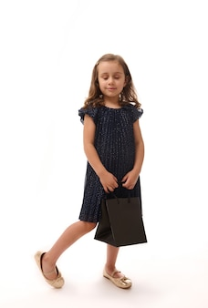 Conceito de black friday. retrato de corpo inteiro isolado em fundo branco com espaço de cópia de uma adorável menina criança de 4 anos vestida em traje de noite e sapatos dourados, segurando um pacote de compras.