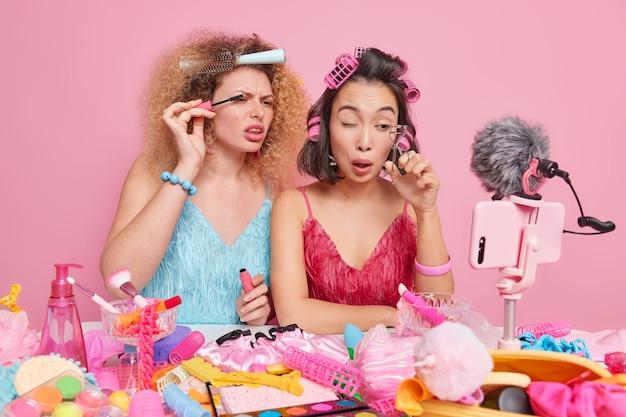 Conceito de blog de beleza. duas mulheres fazendo maquiagem, gravando vídeo, aplicando rímel