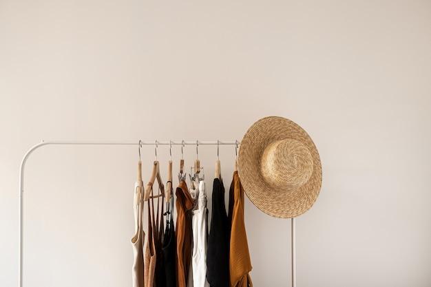 Conceito de blog influenciador de moda minimalista estética. vestido feminino de verão, tops, camisetas, chapéu de palha no cabideiro na parede branca