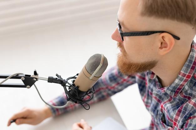 Conceito de blogger, streamer e pessoas - close-up de um jovem dj trabalhando no rádio