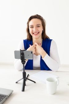 Conceito de blogging e vlog - jovem blogueira falando na câmera.