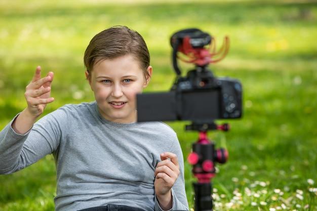 Conceito de blogging e vlogging, menino feliz e sorridente ou blogueiro com videoblog de gravação de câmera na floresta externa