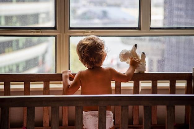 Conceito de bloqueio: uma criança em um berço olha pela janela em uma rua da metrópole
