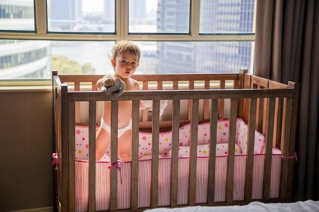 Conceito de bloqueio. uma criança em um berço olha pela janela para uma rua da metrópole ...