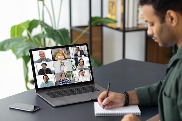 Conceito de brainstorm de grupo, funcionário indiano usa laptop para reuniões on-line com diversos colegas multirraciais sentados no local de trabalho