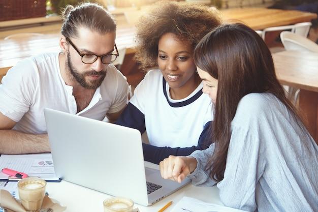 Conceito de brainstorm. grupo multiétnico trabalhando em cafeteria, desenvolvendo estratégia de negócios usando laptop, procurando concentrado.