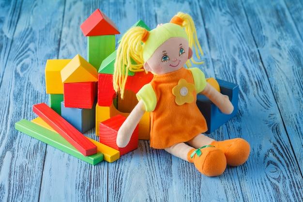 Conceito de brincadeira de bebê, boneca de pano e blocos de madeira para brincar