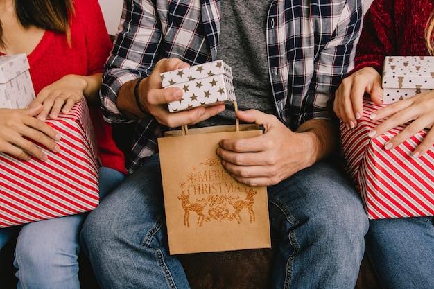 Conceito de brindar de natal com amigos segurando saco e presentes