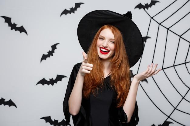 Conceito de bruxa de halloween - bruxa de halloween feliz apontando o dedo lateral sobre uma parede cinza escura com morcego e teia de aranha.