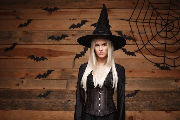 Conceito de bruxa de halloween - bruxa de halloween feliz segurando posando sobre parede de madeira velha.
