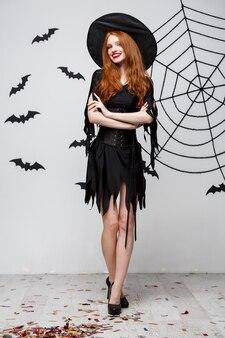 Conceito de bruxa de halloween com o comprimento total de bruxa feliz de halloween segurando posando sobre uma parede cinza escura com morcego e teia de aranha