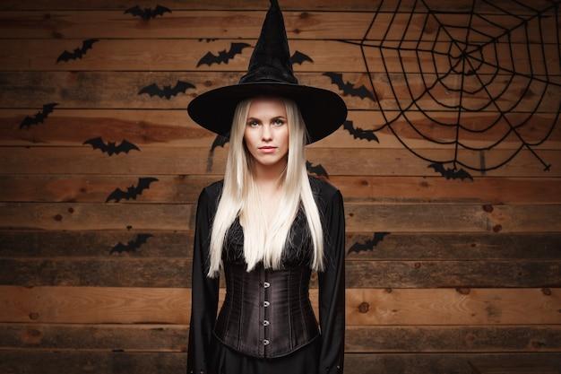 Conceito de bruxa de halloween feliz bruxa sexy de halloween segurando posando sobre o fundo do velho estúdio de madeira
