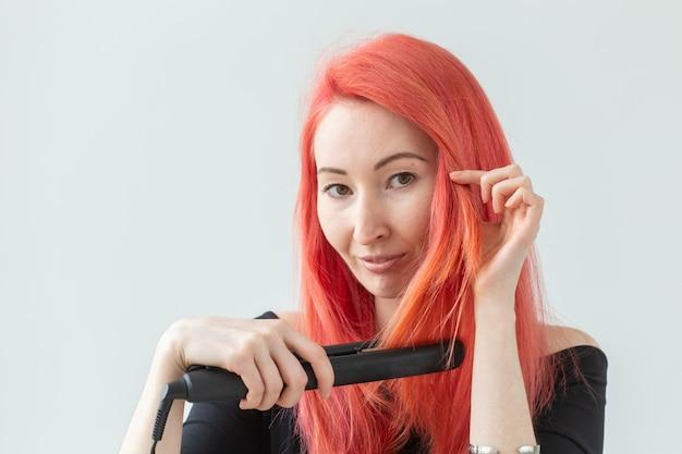 Conceito de cabeleireiro, cabeleireiro e pessoas - jovem mulher com cabelos coloridos, segurando modelador de cabelo sobre fundo branco.