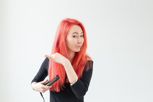 Conceito de cabeleireiro, cabeleireiro e pessoas - jovem mulher com cabelos coloridos segurando um modelador de cabelo