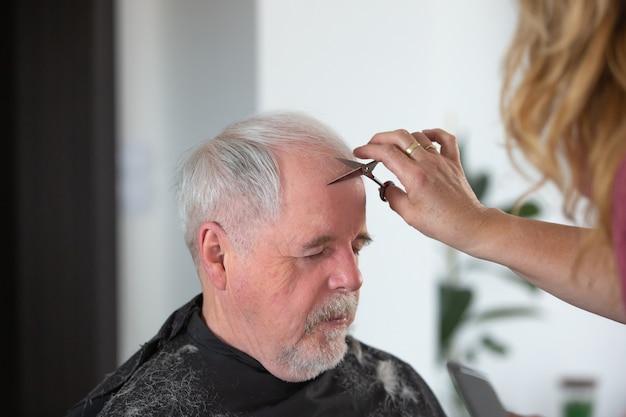 Conceito de cabeleireiro em casa, homem sênior, corte de cabelo por mulher cabeleireira