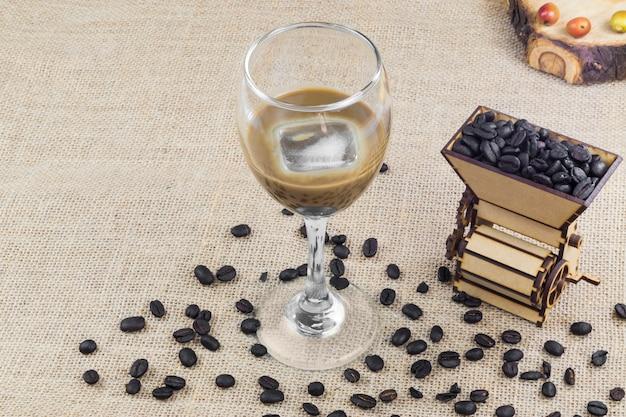 Conceito de café colombiano isolado com uma máquina de moer, grãos de café e uma xícara de creme de café gelado