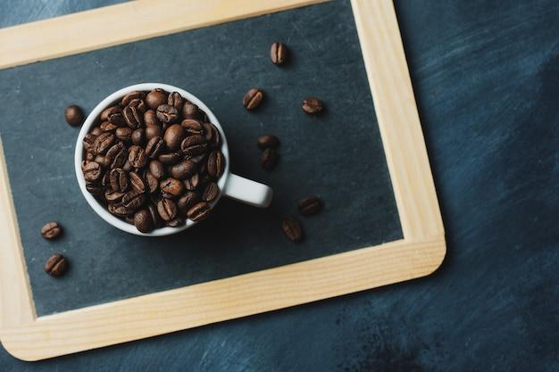 Conceito de café com grãos de café na xícara na mesa escura. vista do topo.