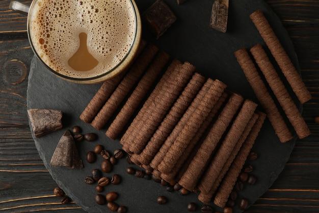 Conceito de café da manhã com rolinhos de wafer de café e chocolate na madeira