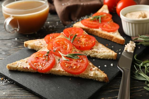Conceito de café da manhã com torradas com tomate em fundo de madeira