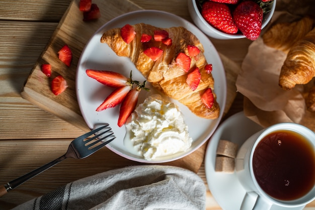Conceito de café da manhã com uma xícara de café, croissants, creme e frutas frescas.