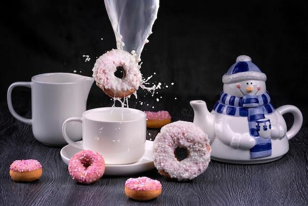 Conceito de café da manhã de natal com donut voando com esguicho de leite e boneco de neve bule