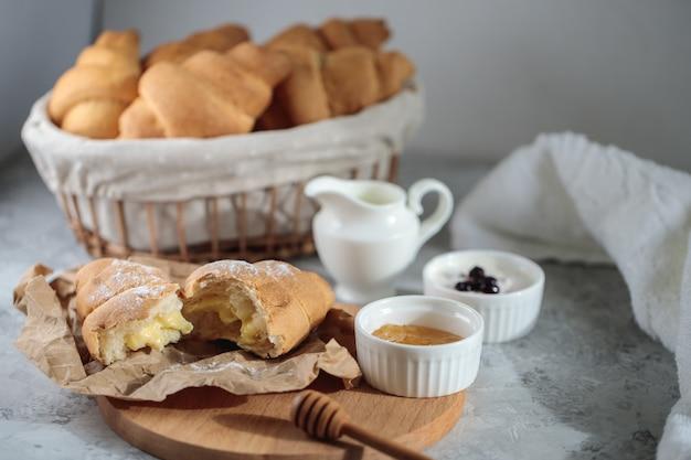Conceito de café da manhã delicioso, close-up. um croissant quebrado com creme está sobre uma tábua de madeira, com uma tigela de mel e um jarro de creme.