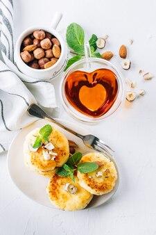 Conceito de café da manhã ou almoço. panquecas de queijo cottage com mel, nozes e hortelã no fundo branco