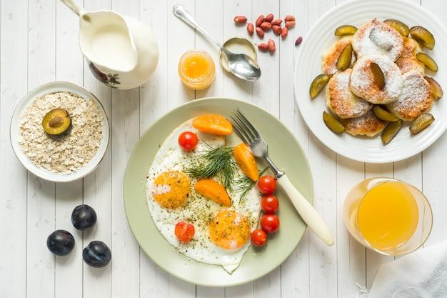 Conceito de café da manhã. ovos fritos, panquecas de queijo cottage, ameixas e aveia com leite, suco de laranja em cima da mesa