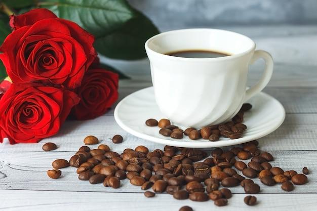 Conceito de café da manhã romântico. xícara de café branca, grãos de café e rosas vermelhas em fundo cinza claro.