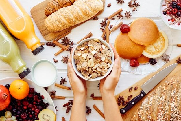 Conceito de café da manhã saudável com mãos segurando cereais