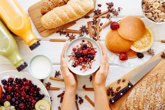 Conceito de café da manhã saudável com mãos segurando iogurte
