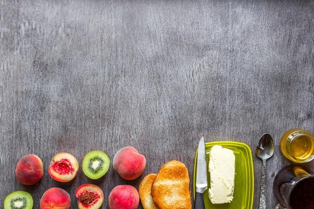 Conceito de café da manhã saudável torradas com manteiga, mel, frutas e chá sobre fundo escuro de madeira.
