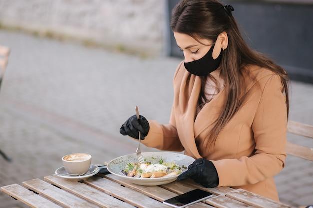 Conceito de café de quarentena no terraço. mulher jovem e atraente sentado no café sozinho. mulher comendo durante o intervalo.