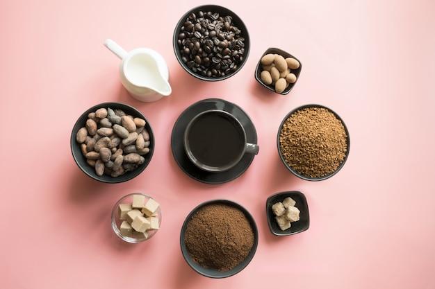 Conceito de café, grãos de cacau e açúcar diferente na rosa.