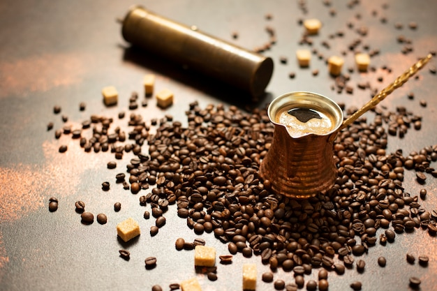 Conceito de café turco. bule de café de cobre (cezve), moedor de café vintage, grãos de café e açúcar em um fundo escuro e vintage. fechar-se