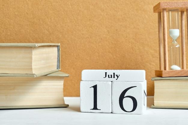 Conceito de calendário de 16 de julho dia décimo sexto dia em blocos de madeira.