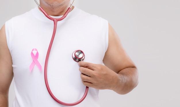 Conceito de câncer de mama em homens: retrato de homem asiático segurando o estetoscópio e a fita rosa, o símbolo da campanha de câncer de mama.
