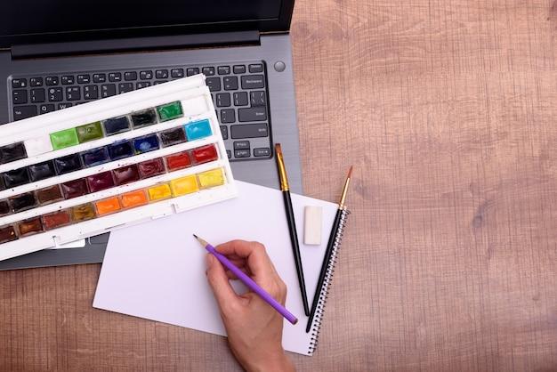 Conceito de capa de aula de desenho online com folha de laptop de tintas e pincéis de papel no escritório de madeira.