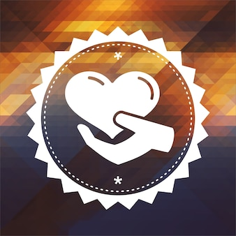 Conceito de caridade - ícone do coração na mão. design de rótulo retrô. fundo de hipster feito de triângulos, efeito de fluxo de cor.