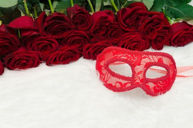 Conceito de carnaval romântico. máscara de carnaval vermelho e um buquê de rosas vermelhas em pêlo branco.