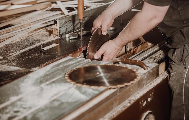 Conceito de carpintaria e madeira, marceneiro profissional, carpinteiro trocando a lâmina de serra, artesanato e manufatura